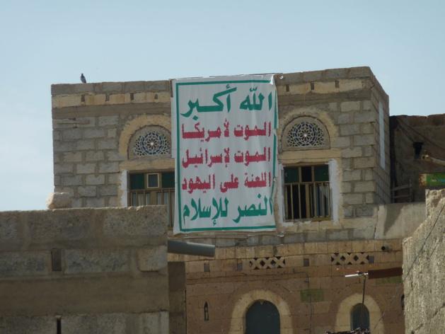 Maison à Dhamar, sud-ouest du Yémen, arborant en septembre 2013 l'emblème des Houthis : « Dieu est grand / Mort à l'Amérique / Mort à Israël / Malheur sur les juifs / Victoire à l'islam ». Crédit : Abdullah Sarhan (licence CC BY-SA 4.0)